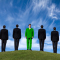 Conceptual image of businessmen on a hilltop with one dressed in green suit looking in the opposite direction. Environmental concern issues - how green are you? Looking for a greener future etc.